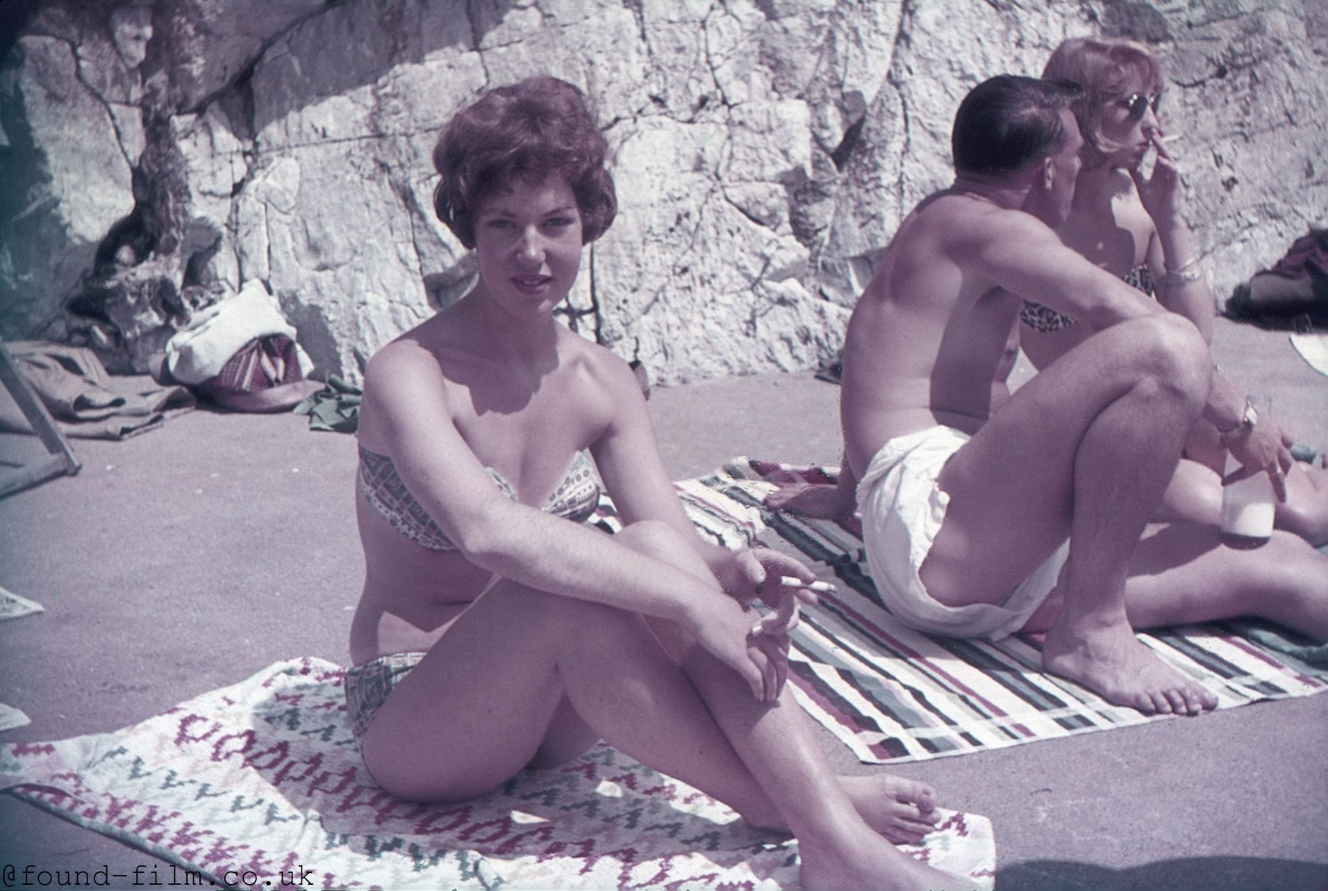 A Pretty girl sitting on a towel with a cigarette