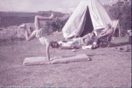 A Girl performing gymnastics on the lawn c1955