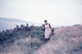 A Woman walking along a coastal path in the mid 1950s