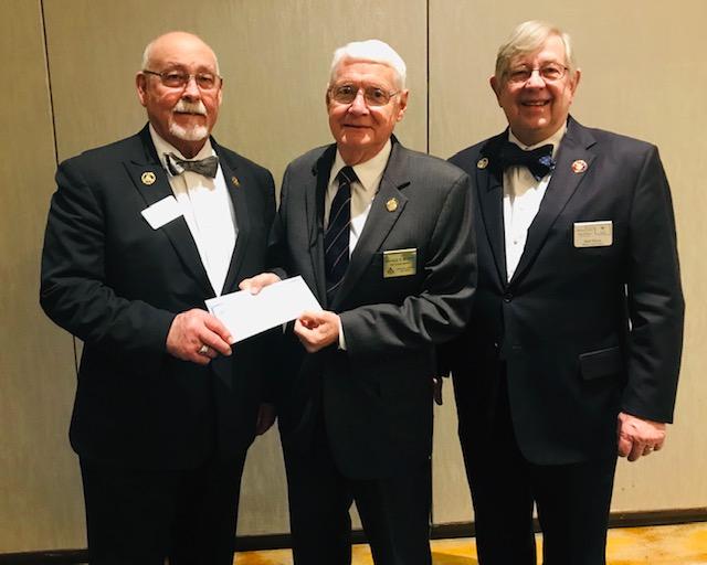 George Braatz, Foundation Trustee, receives the $100,000 check from John Logan, Executive Director, and Secretary Robert G. Davis