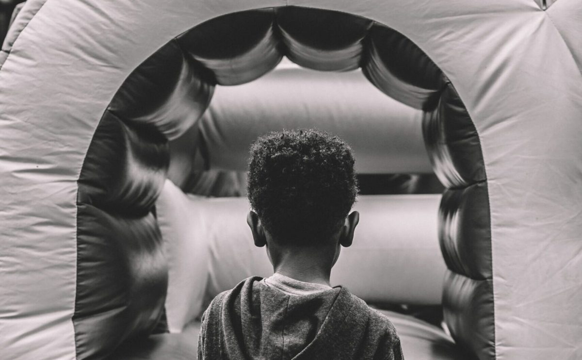 Boy standing in front of a bouncy house