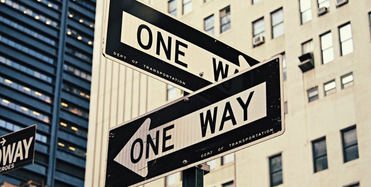 Two One-Way signs at a city intersection
