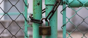 A lock and chain on a teal fence