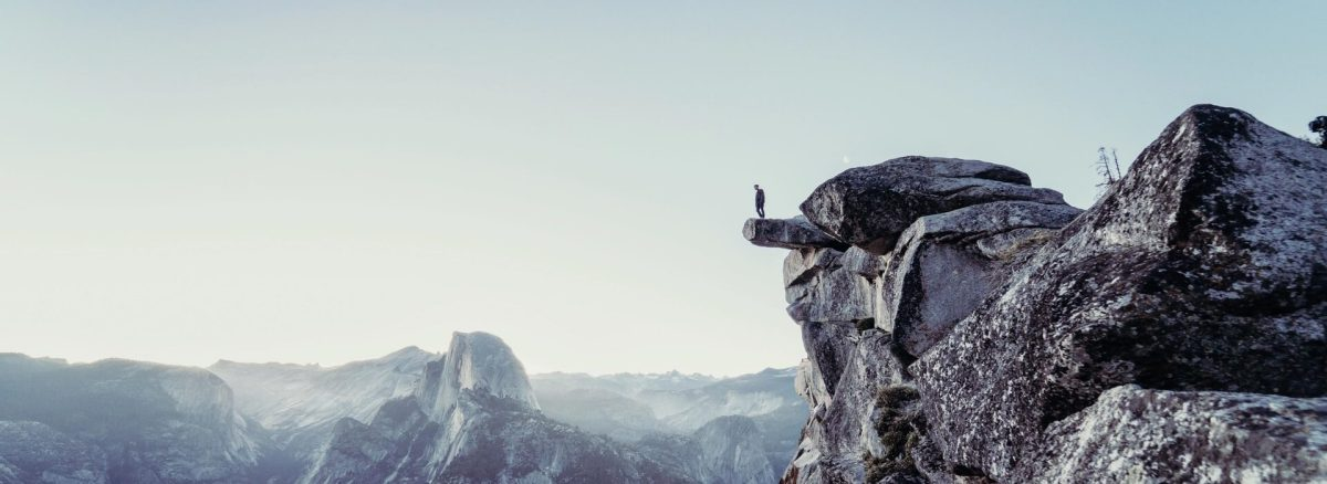 Man standing on the edge of a cliff, looking down.