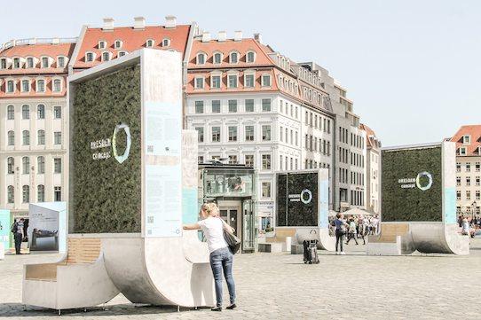 Passanten schauen sich die City Trees auf dem Dresdner Neumarkt an. Foto: Green City Solutions