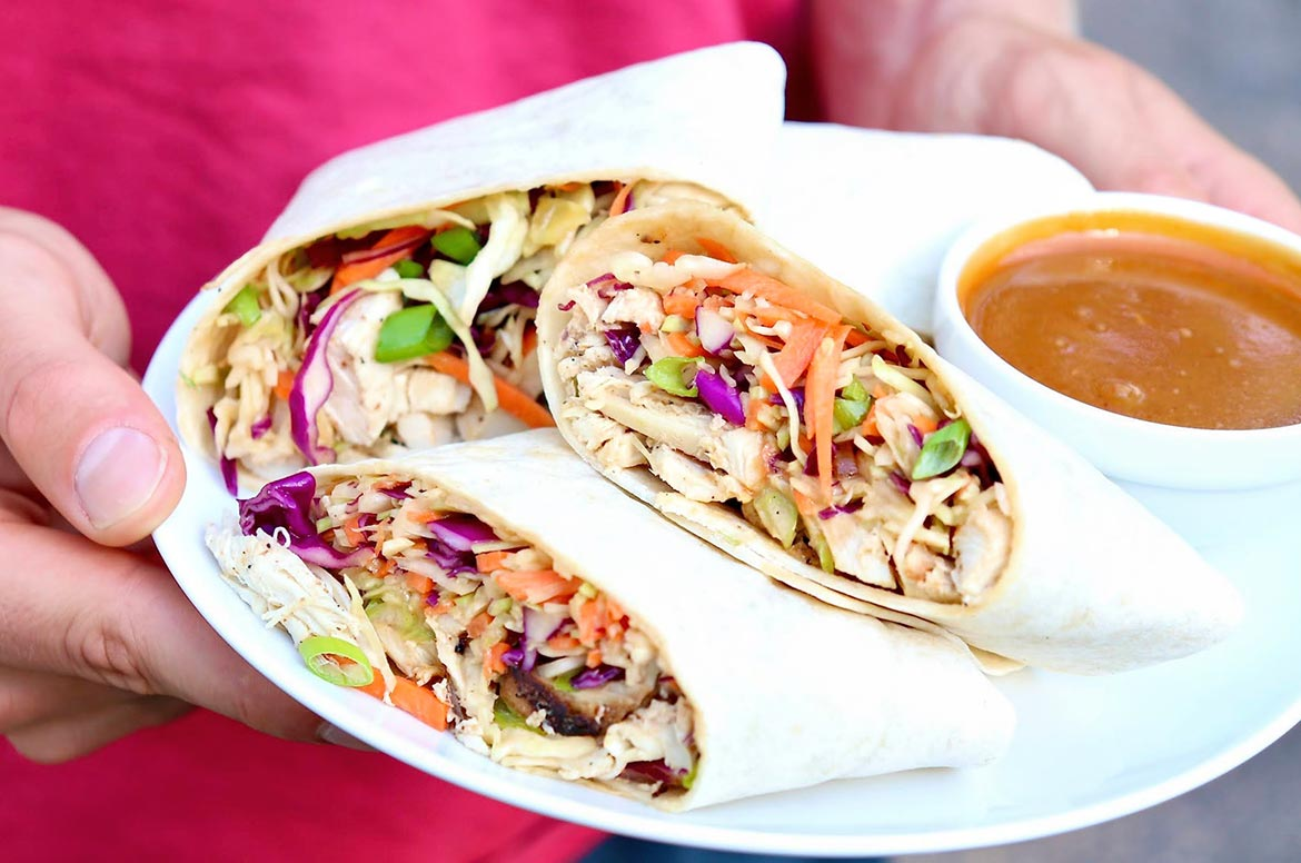 Crunchy slaw and protein-rich chicken are bathed in a peanutty dressing then rolled into a handy wrap in this Asian-inspired meal that is sure to become a family favorite. As an option, feel free to skip a step and serve the chicken and slaw as a hearty, healthy salad!