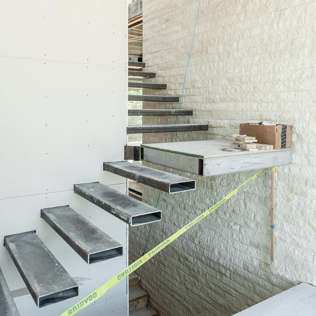Steel and Stone make up the foundation for a 4 story staircase. Built by @foursquarebuilders designed by photo by @redpantsstudio