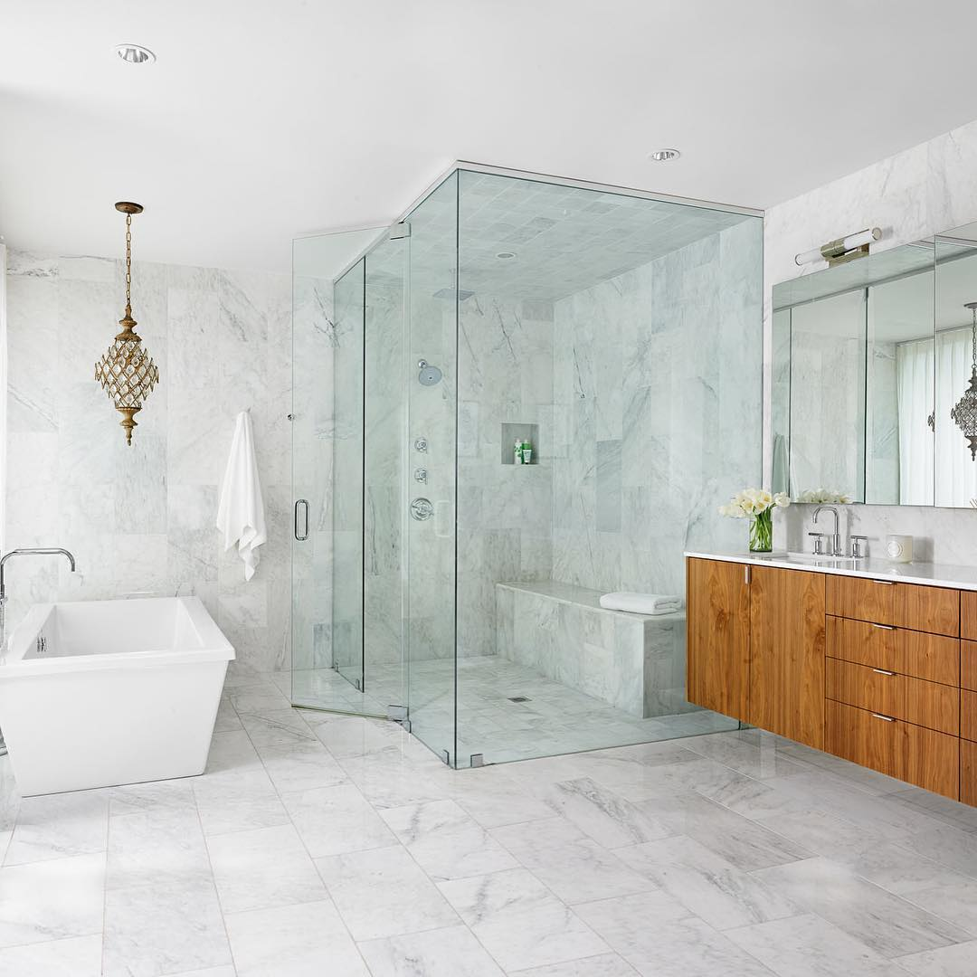 Marble on marble with a splash of walnut make for a spa like bathing experience. Built by @foursquarebuilders