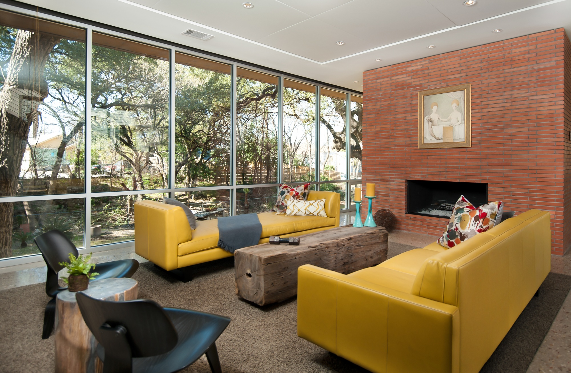 Floor to ceiling glass open up the outdoors to this cozy living room.