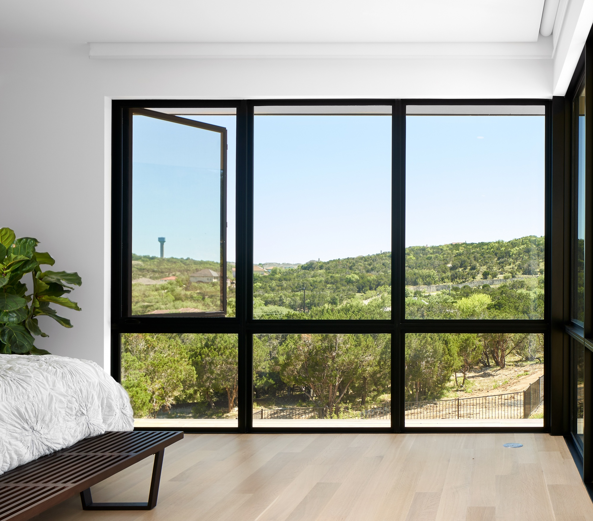 Well positioned master bedroom welcomes hill country and pool side views.