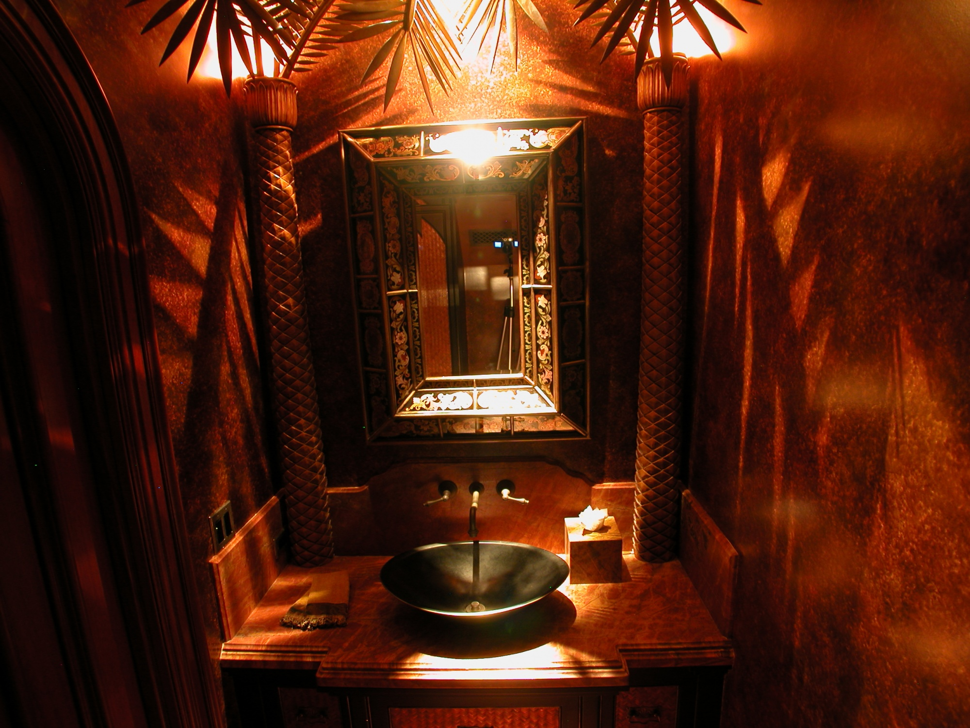 Hand carved palm trees are featured in this powder bath.