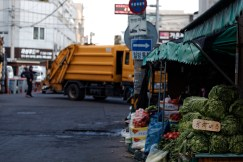 Cabbage is stacked for sale while a man directs a garbage truck at the intersection.