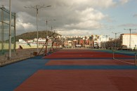 Tennis and basketball courts line a portion of the seaside amusement area in Jeju City.