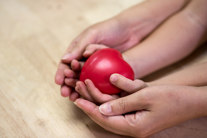 Red heart in child kid and mother hands on wooden table.