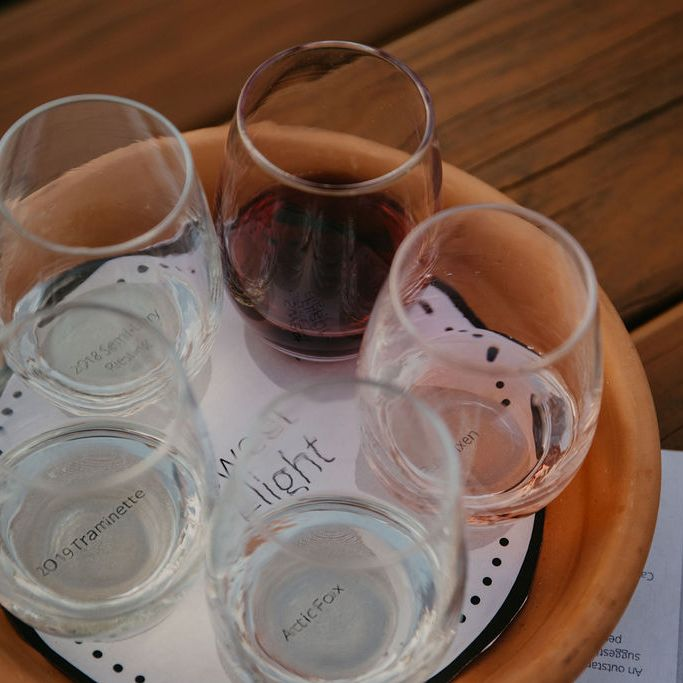 A flight of five wines in stemless glasses on a terracota tray