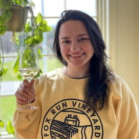 Jill Dinan, Cafe Manager holding a glass of wine in front of the window at Fox Run Cafe