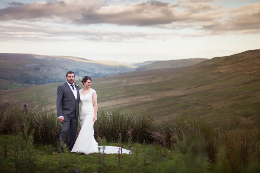 Simonstone Hall wedding photography | Bride and groom stand in front of Swaledale, Yorkshire Dales hills backdrop