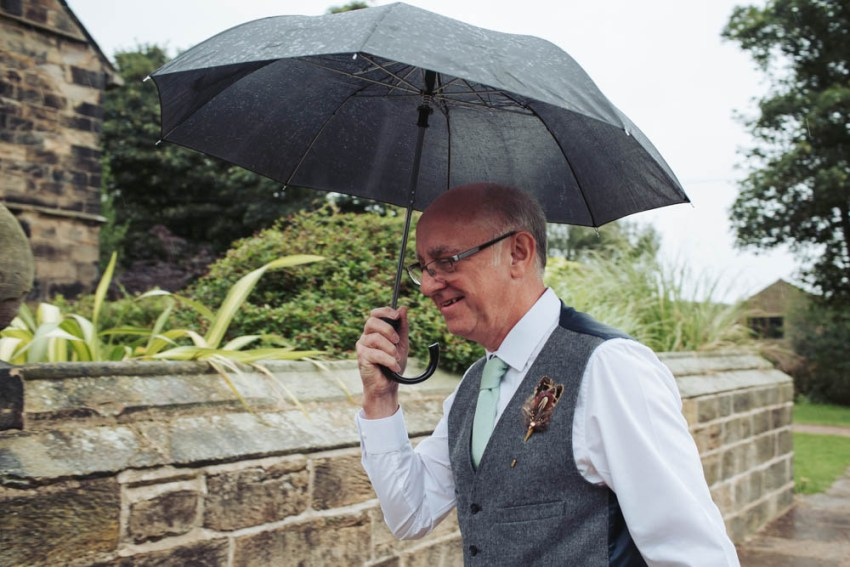 Farther of groom with umbrella in rain
