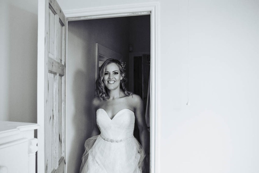 Bride enters room smiling wearing lace dress