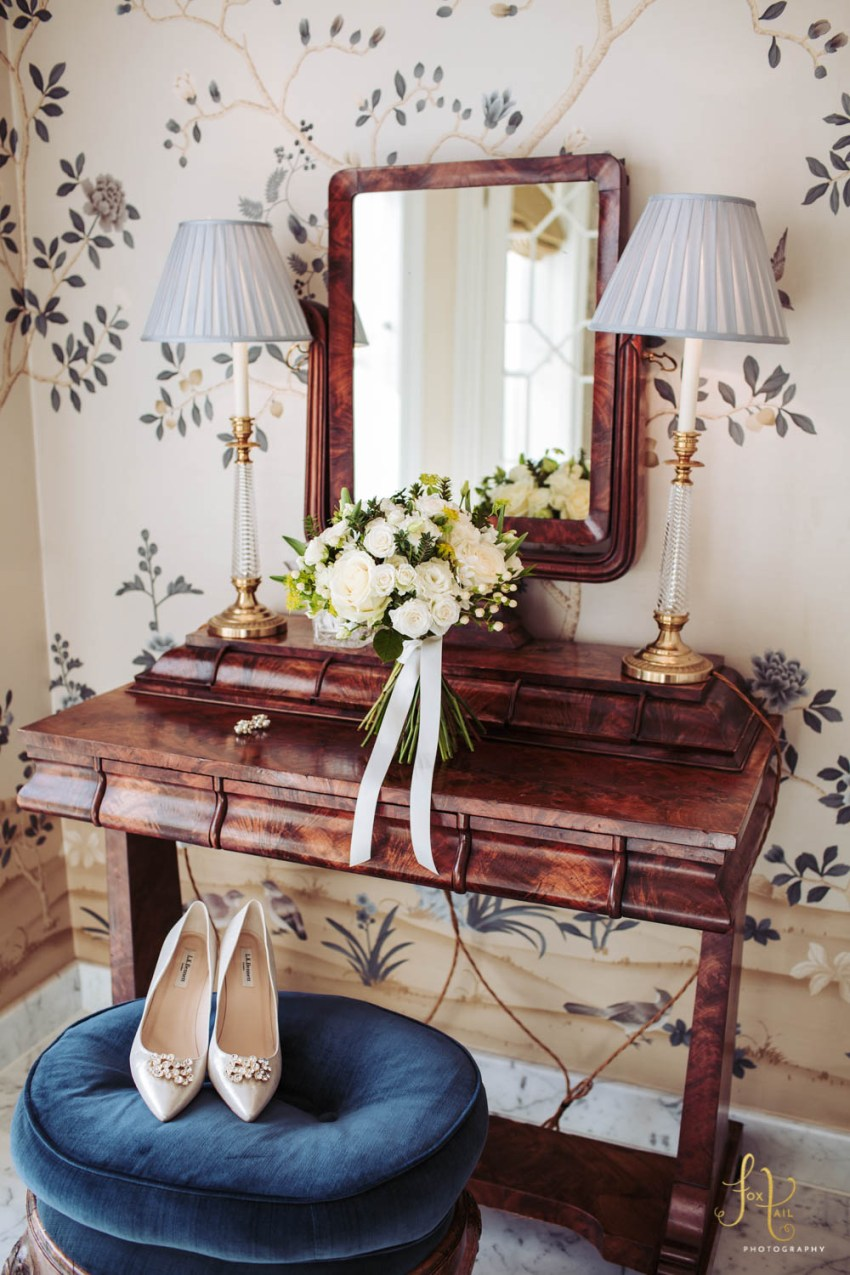 Wedding shoes and bouquet displayed with dressing table at Cliveden House