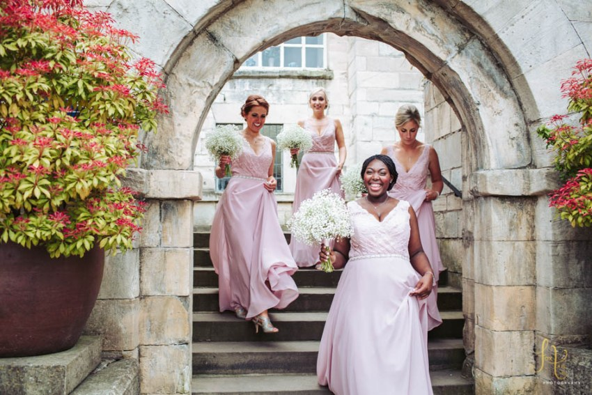 Brides maids wear pink dresses by Alfred Angelo. Documentary wedding photography at Hazlewood in Yorkshire.