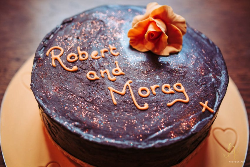 Chocolate cake decorated with orange text and orange rose. Vow renewal cake for the congregation of St. Michael's Church in Grassington.
