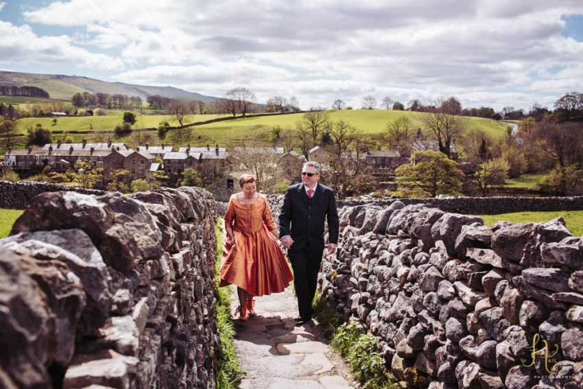 Grassington wedding photography. Couple walking up to Grassington from Linton Falls. Dry stone walls and rolling hills of the Yorkshire Dales in the backdrop.