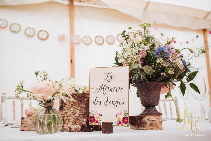 Rustic themed wedding decorations at head table in marquee.