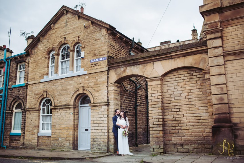 Victoria Hall wedding photography, Saltaire, Yorkshire. Bride and groom stand in front of Saltaire village home.