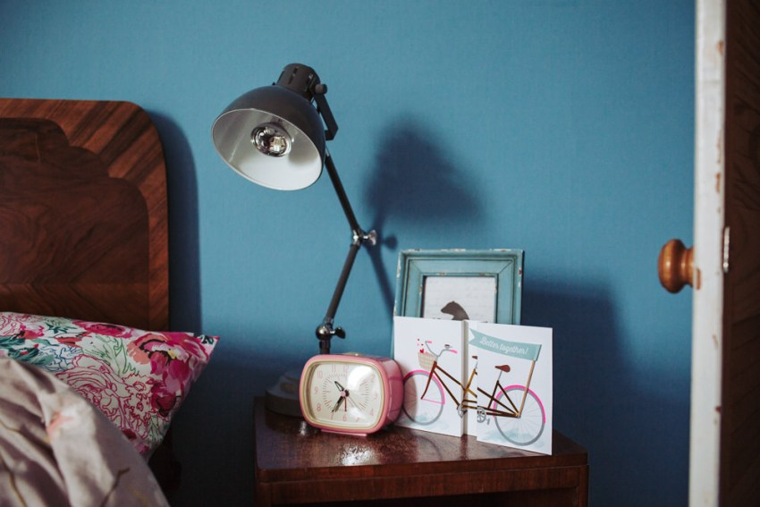 Tandem bicycle wedding card on bedside cabinet with retro pink clock.