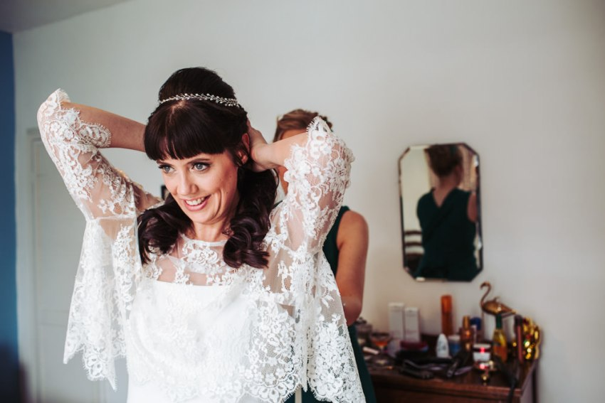 Bride puts on french lace jacket over her wedding dress.