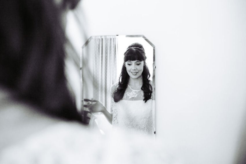 Bride admires her reflection in mirror wearing wedding dress. Victoria Hall wedding photographer, Saltaire, Yorkshire.