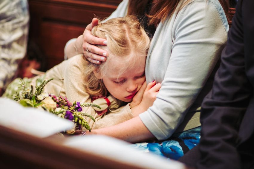 Flower girl sleeps on mothers lap during wedding ceremony