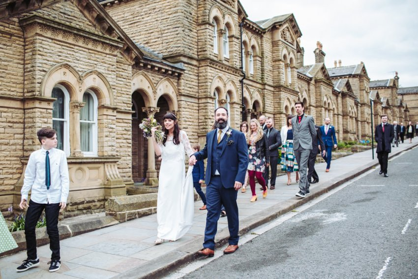 Bride and groom walk with wedding guests through Saltaire to Victoria Hall