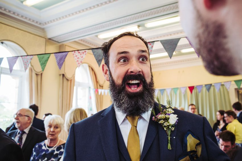 Happy and surprised groom face at Victoria Hall wedding.