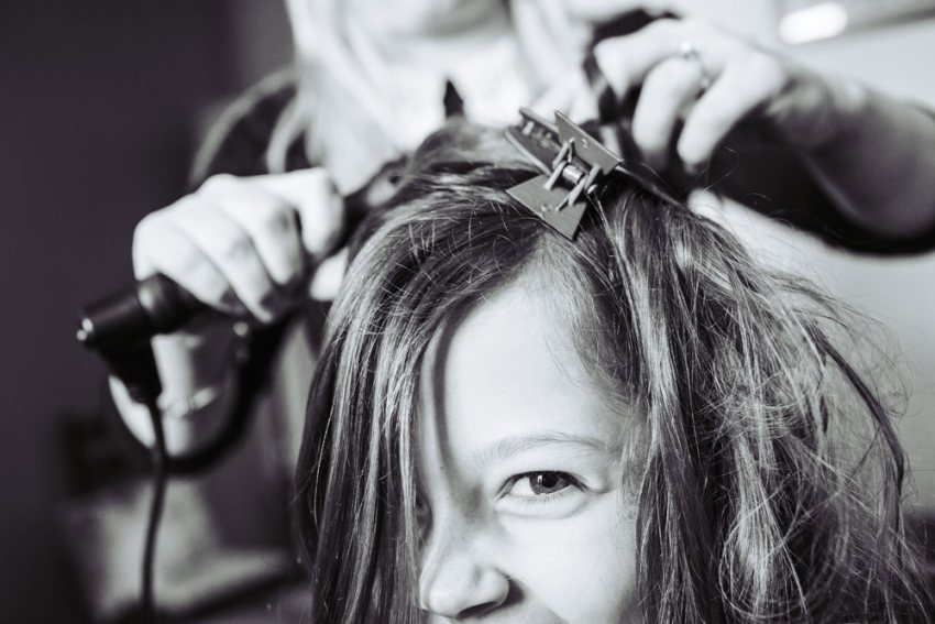 Gild peeking out from hair while hairdresser fixes her hair for a wedding.