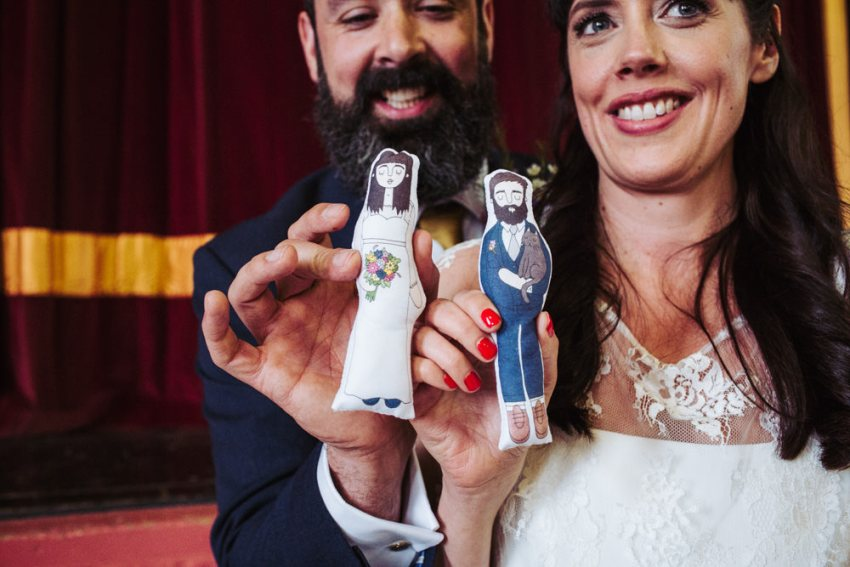 Bride and groom with fabric cake toppers of cartoon versions of themselves.