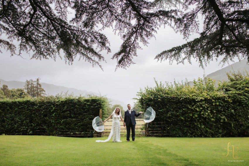 New Dungeon Ghyll wedding photography in Lake District rain. Bride and groom with umbrellas