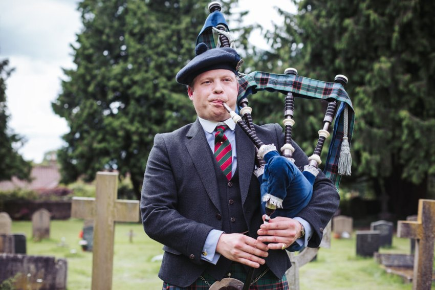 Man plays bagpipes while guests arrive at the church in Staveley.