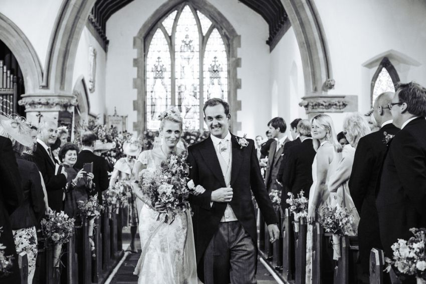 All Saints Church wedding in Staveley, York. Bride and groom walk down the isle.