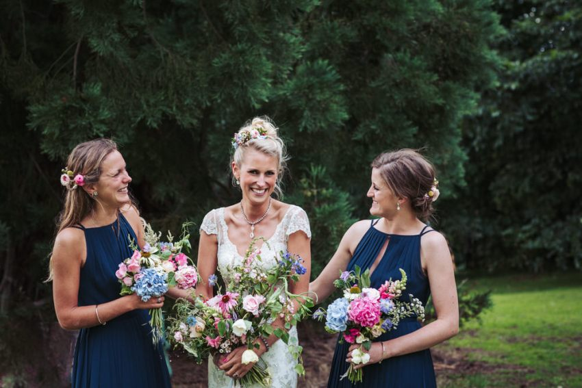 Bride in Liliana Dabic wedding dress, bridesmaids wear navy blue Ted Baker dresses holding Manor Garden bouquets. Natural York wedding.