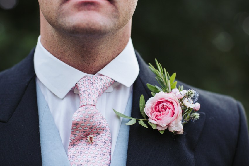 Detail photography of groom with pink patterned tie and pink rose buttonhole by Manor Garden wedding florist.