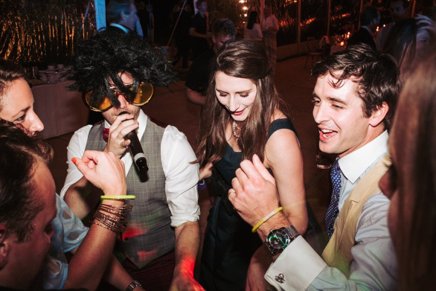 Singer in elvis glasses with wedding guests on the dance floor.
