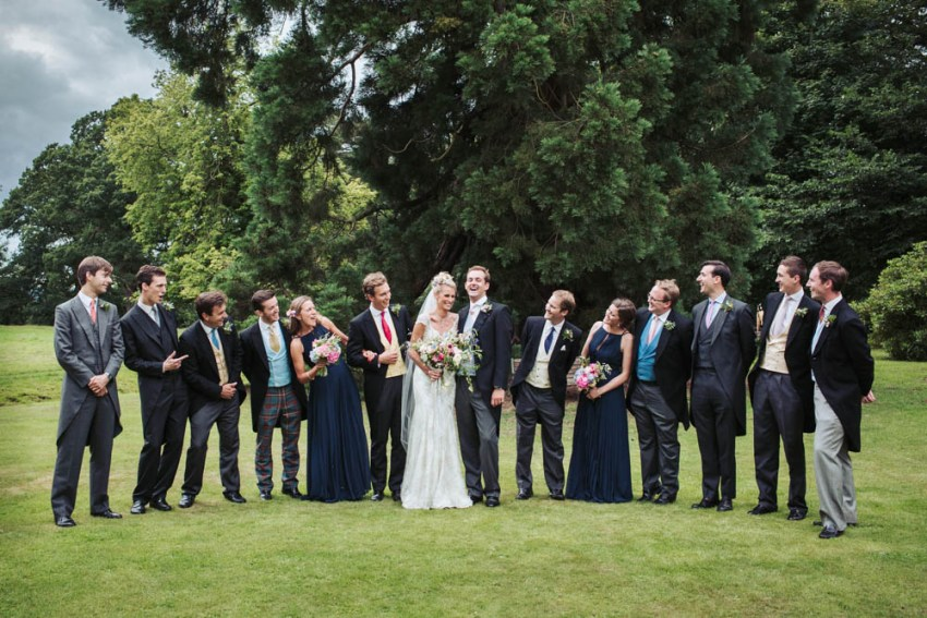 The bridal party. Bridesmaids wear navy blue with groomsmen in pastel yellow and blue waistcoats.