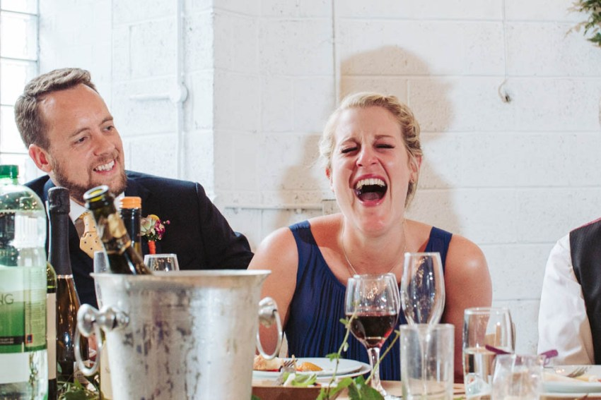 Bridesmaid laughs during speeches.