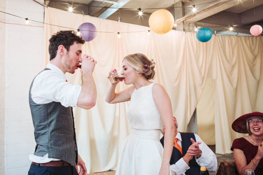 Bride and groom drink their fist shot together as husband and wife.