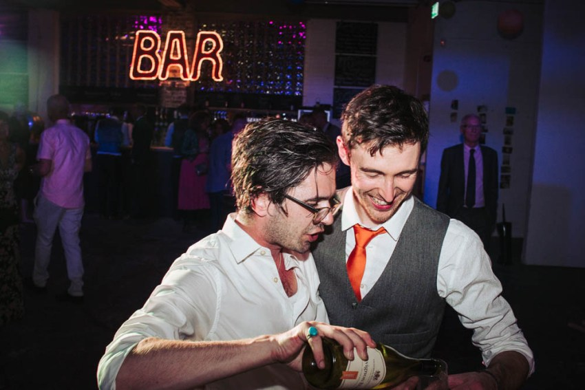 Groom having his drink topped up by a friend.
