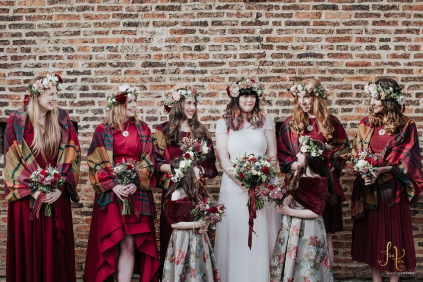 Bridesmaids in red tartan shawls with flower crowns