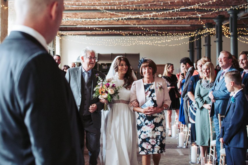 Bride walks down the isle with her mother and father at the Arches wedding venue.