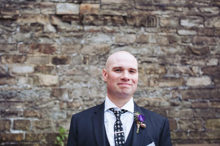 The groom smiles, wearing an Alexander McQueen tie and purple buttonhole.